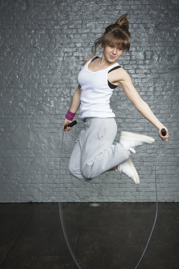 Gentille jeune fille sautant sur la corde de saut photographie stock