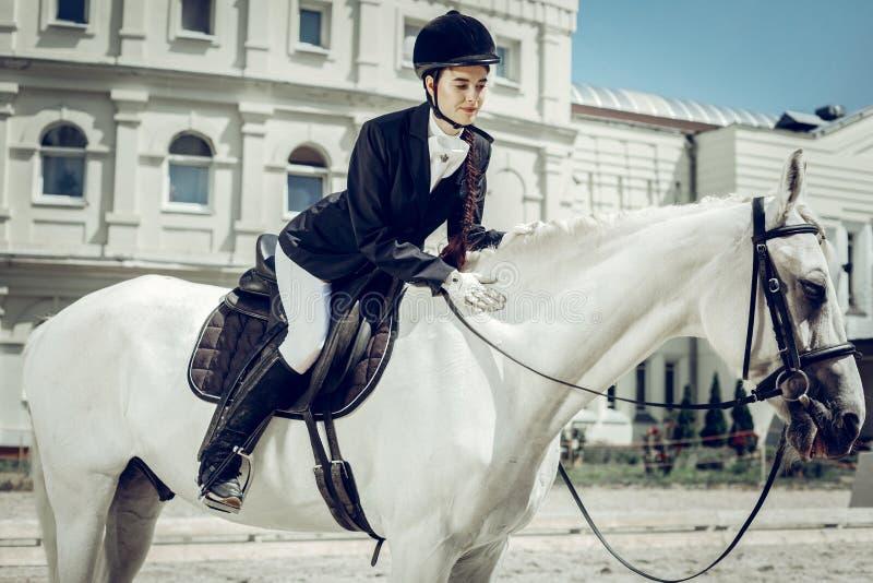 Gentille jolie jeune femme s'asseyant sur le cheval photo stock