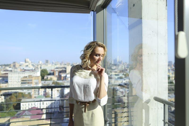 Gentille personne féminine se tenant au restaurant près de la fenêtre avec le fond de paysage urbain photo libre de droits