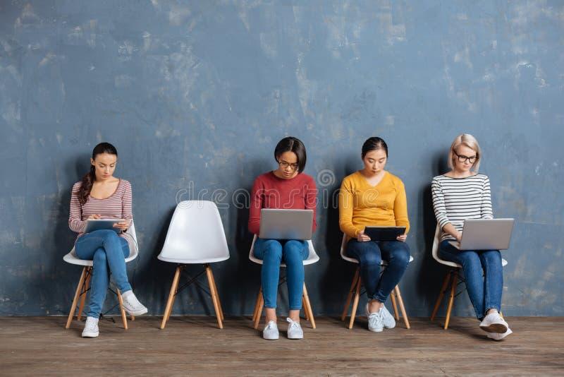 Gentilles jeunes femmes à l'aide de leurs dispositifs image stock