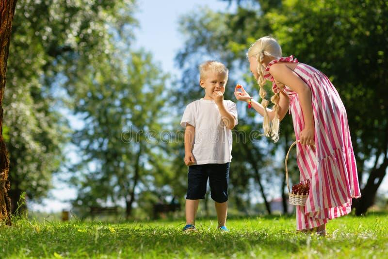 Gentils enfants mangeant des fruits en parc photo libre de droits