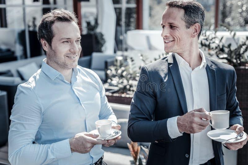 Gentils hommes d'affaires avec plaisir appréciant leur café image libre de droits
