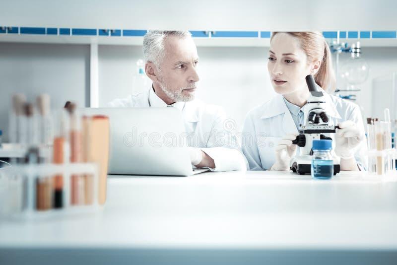 Gentils scientifiques professionnels s'asseyant ensemble images stock