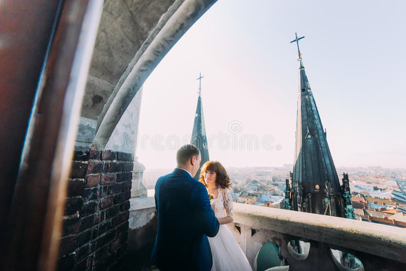 Gentle beautiful bride and groom holding hands embracing face-to-face on the ancient balcony, background cityscape royalty free stock images