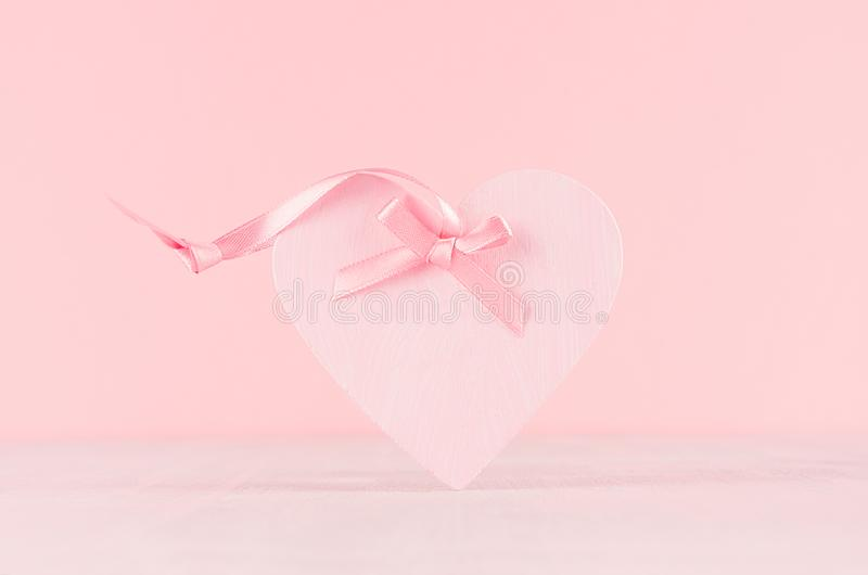 Gentle decor for Valentine days - soft light pink heart with ribbon on white wood board, closeup. Gentle decor for Valentine days - soft light pink heart with royalty free stock photo