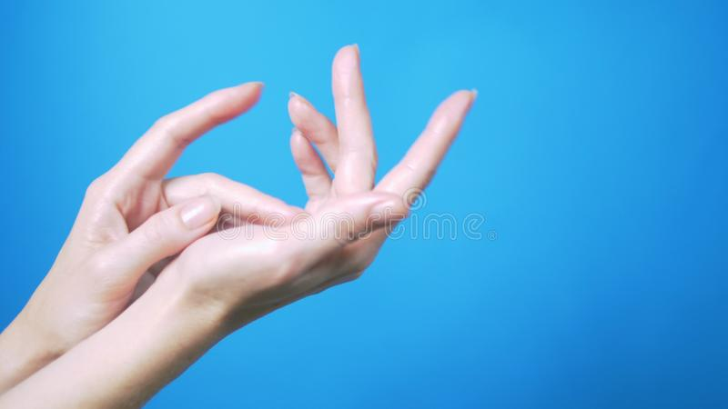 Gentle female hands with natural manicure move beautifully on a blue background. Place for text. royalty free stock photography