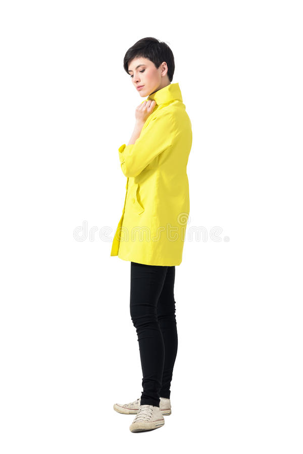Gentle feminine young short hair woman in yellow coat looking down royalty free stock photos