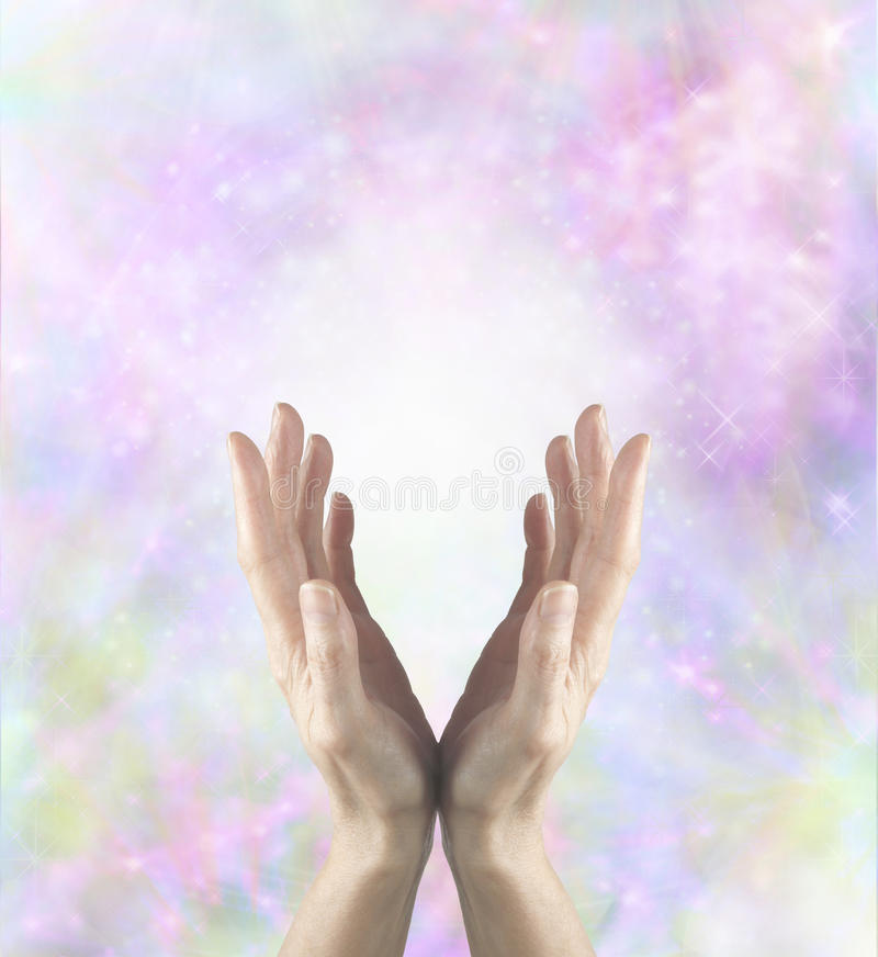 Gentle Healing Energy. Female healing hands cupped and reaching upwards with white light between palms and a beautiful delicate pink and pastel colored stock image