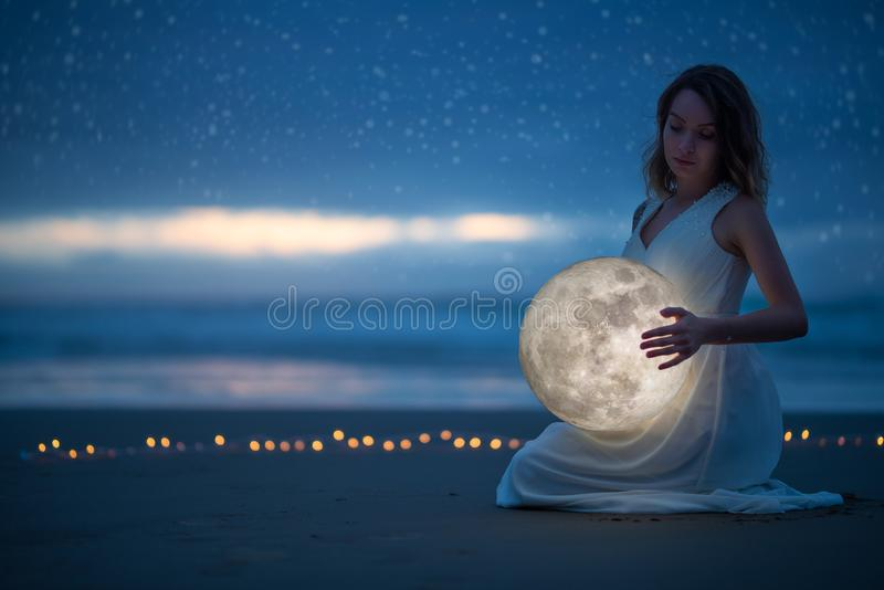 Gentle image of a girl, Astrology, Female magic. Beautiful attractive girl on a night beach with sand hugs the moon, art stock images