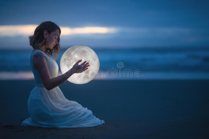 Gentle image of a girl, Astrology, Female magic. Beautiful attractive girl on a night beach with sand hugs the moon, art stock photos