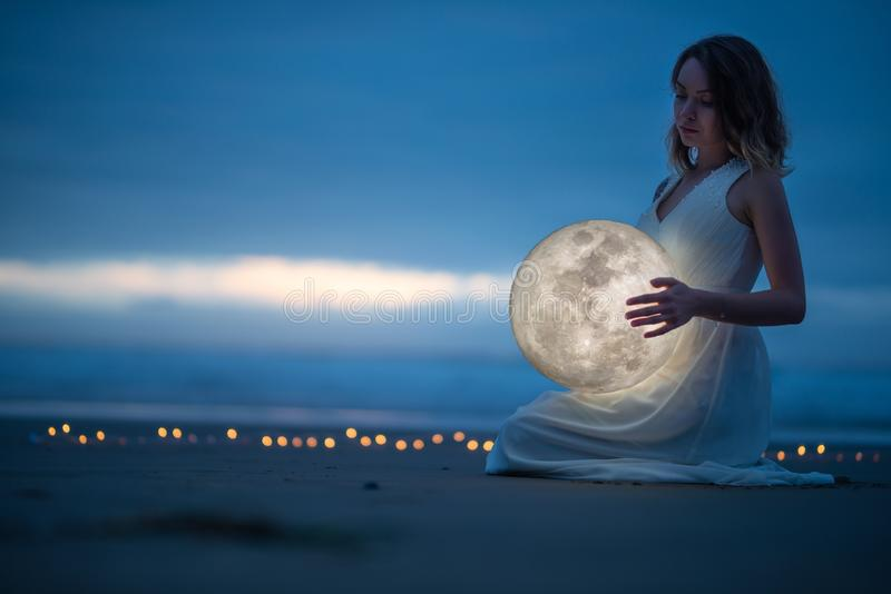 Gentle image of a girl, Astrology, Female magic. Beautiful attractive girl on a night beach with sand hugs the moon, art royalty free stock image