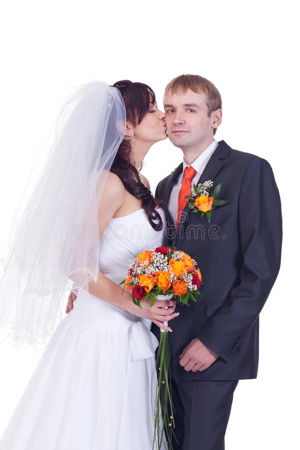 The gentle kiss. Bride gently kisses shy groom royalty free stock photo