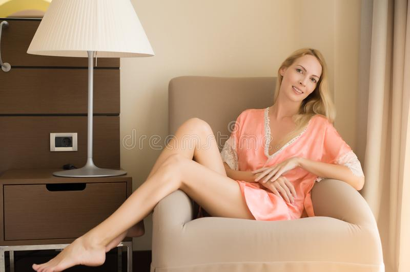 Gentle photo of a young beautiful confident woman in a pink silk robe. She sits in chair with bare feet stock photo