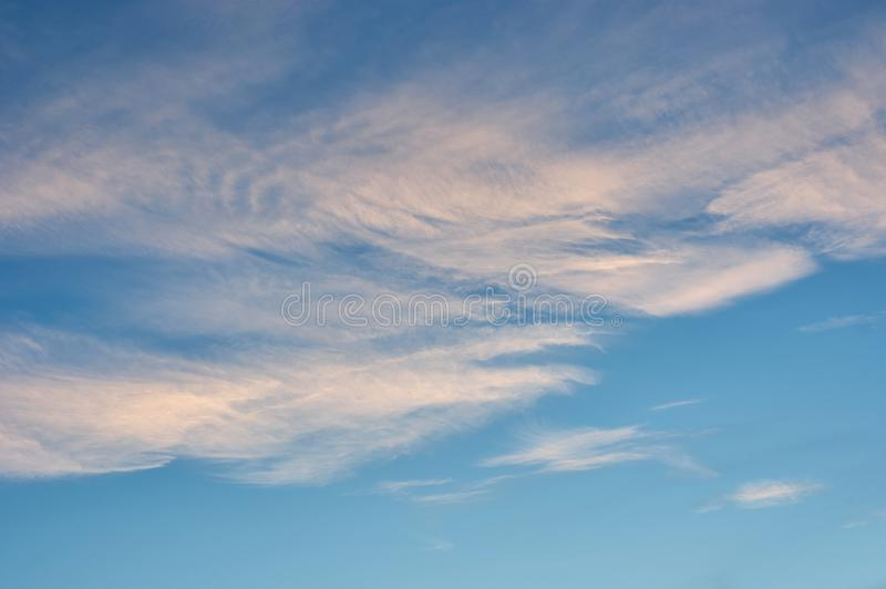 Gentle, pink clouds in the blue sky.  stock images