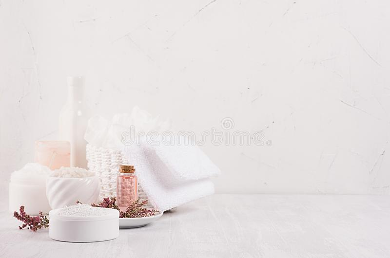 Gentle pink cosmetics oil, small flowers and white soap, cream, clay, towel on white wooden shelf, copy space, vertical. Gentle pink cosmetics oil, small stock photography