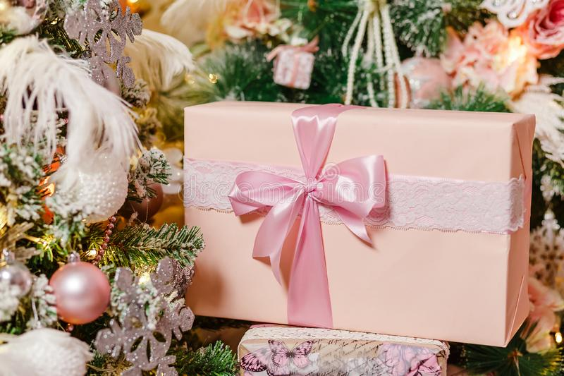Gentle pink gift box under the Christmas tree royalty free stock photos