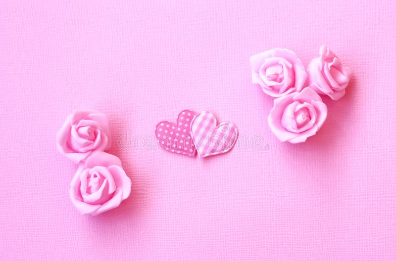 Gentle pink holiday background with two hearts, rose flowers stock photography