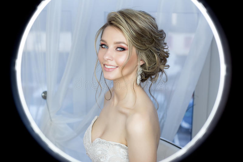 Gentle portrait of a beautiful cute happy bride with a beautiful hairdo festive bright make-up in a wedding dress with earrings an stock images