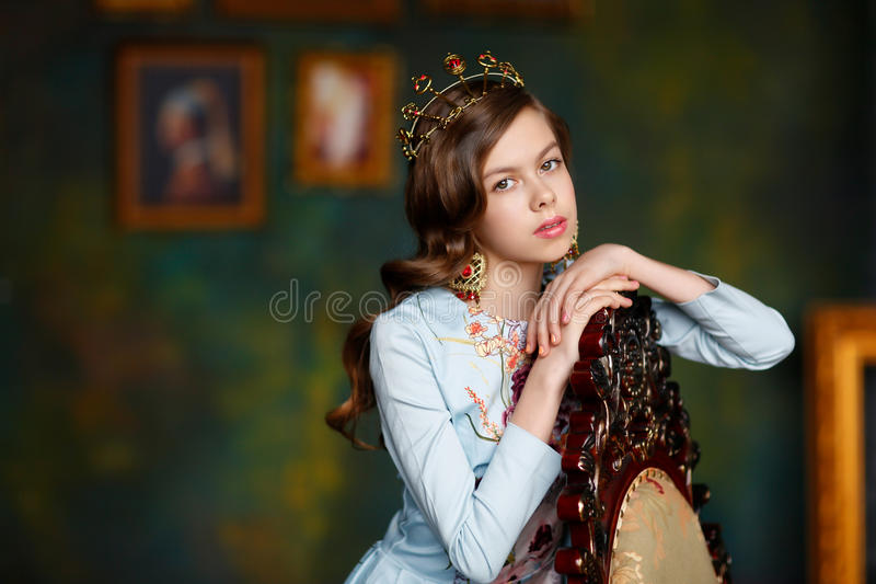 Gentle princess with brown eyes and beautiful hair in red earrin. Gs and a blue dress stands in castle stock images