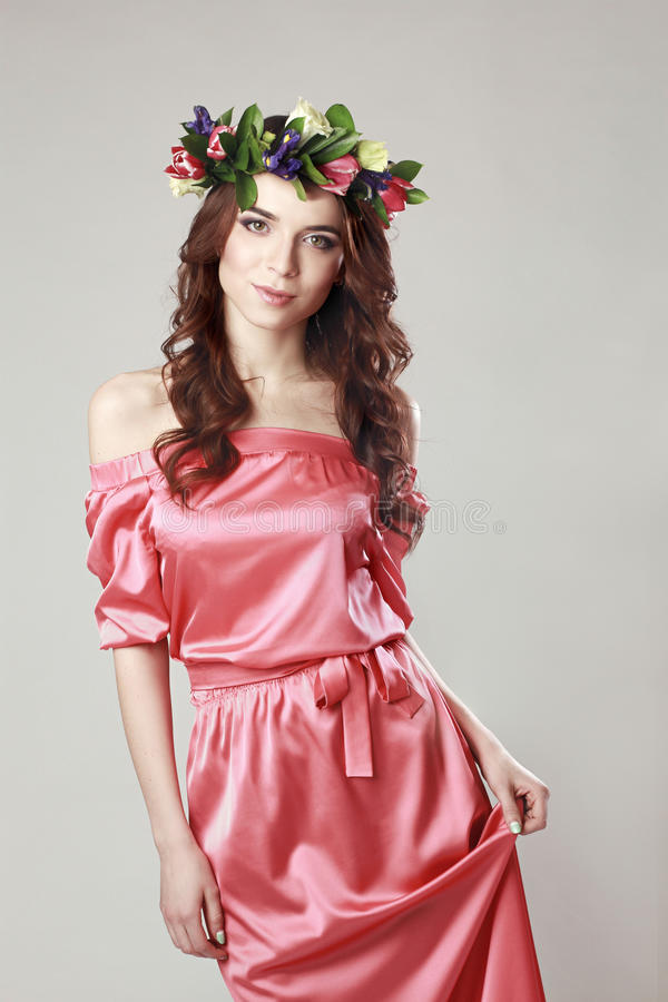 Gentle romantic appearance of the girl with a wreath of roses on her head and a pink dress. Joyful Jolly spring woman. Summer lady. In long pink dress royalty free stock photo