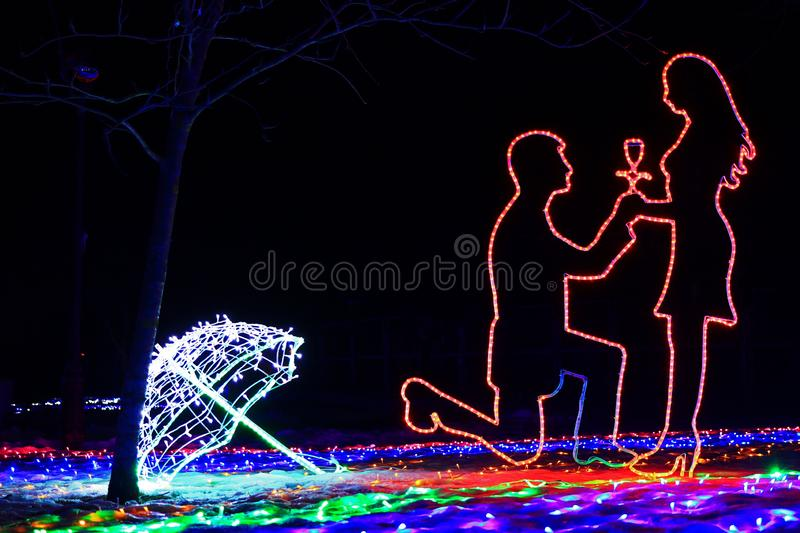 Gentle and romantic contours of a man on his knee who makes a proposal to the woman about the engagement, made by LED tape. Romantic, sensual and tender outlines stock photo