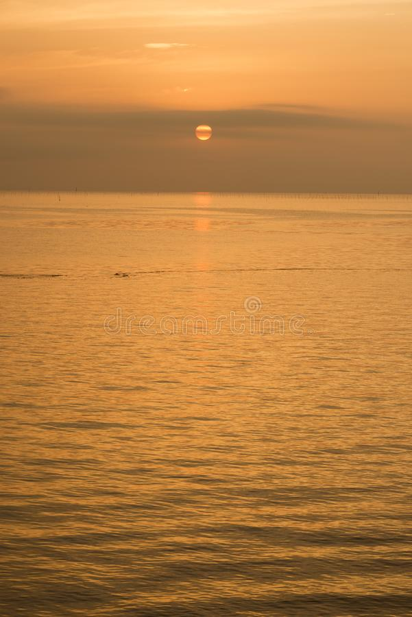 Gentle sea at sunrise. Orange view of gentle sea at sunrise in vertical composition royalty free stock photo