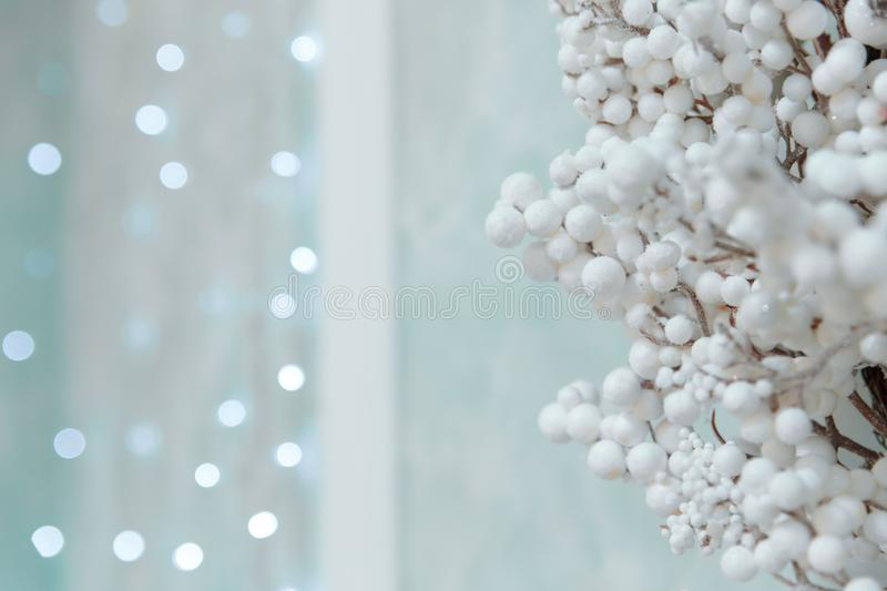 Gentle sky blue Christmas background with bokeh and small white balls on a branch in the foreground. Christmas winter stock photos