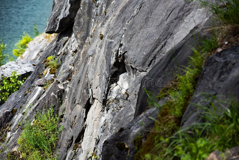 Gentle slope of a marble cliff and water stock images
