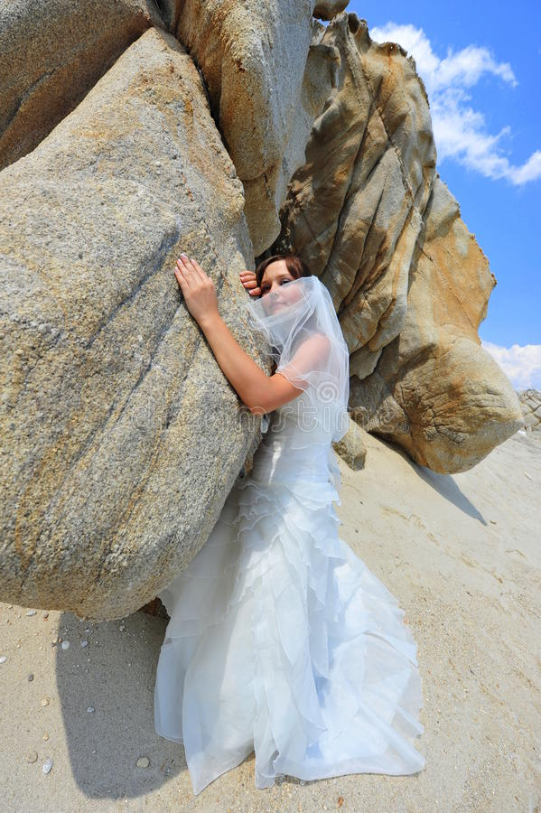 The gentle touch of a bride. Portrait of a beautiful bride touching in gentle way the massive rock stock photography