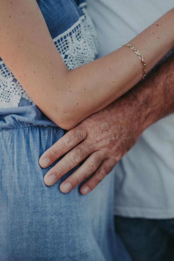 Gentle touch of a man`s hand on a woman`s shoulder royalty free stock photography