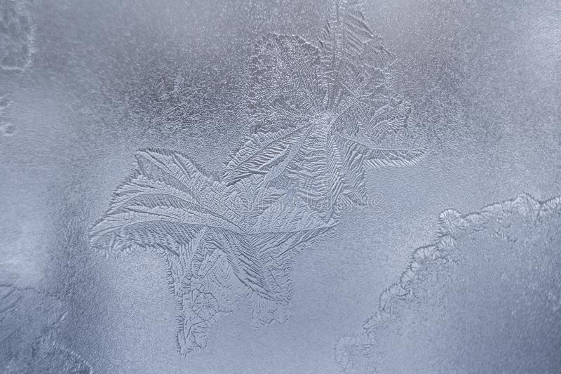 Gentle translucent winter icy pattern similar as leaves at window glass. royalty free stock photo