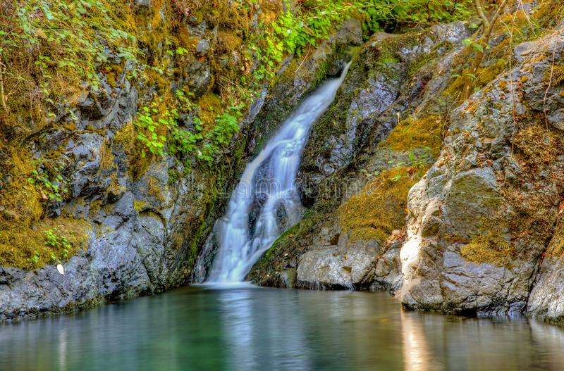 Gentle waterfall pours into a clear pool of water in Rogue River Oregon stock photo