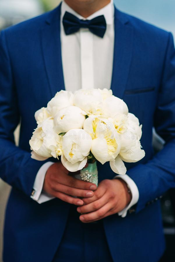 Wedding bouquet of white peonies in the hands of the groom stock photos