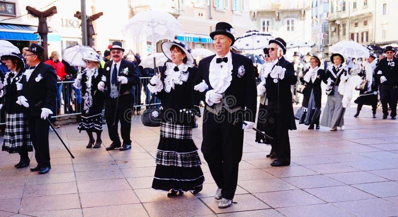 Gentlemän och damer i karnevalprocessionen i Fiume, Kroatien royaltyfri bild