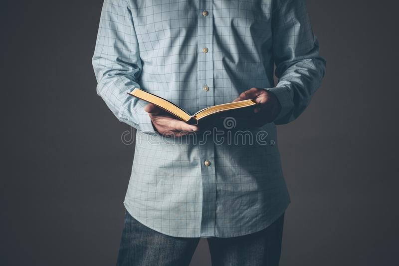 Gentleman with a bible open in his hands royalty free stock photography