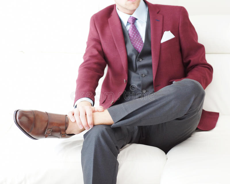 Gentleman Burgundy Blazer Double Monk Shoes. Young male model on a white sofa wearing a burgundy blazer and brown leather shoes royalty free stock photo