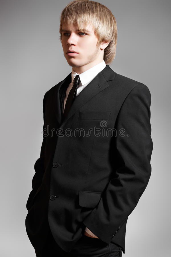 Gentleman business man model in elegant black suit. Portrait of gentleman business man model in elegant black suit on gray background stock photos