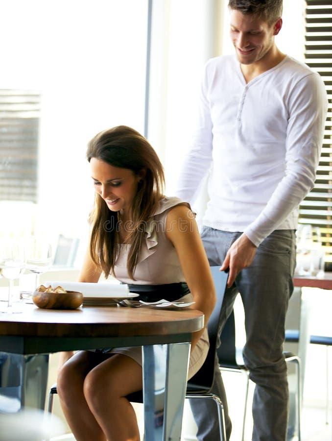 Gentleman Helping Girlfriend to Her Seat stock image