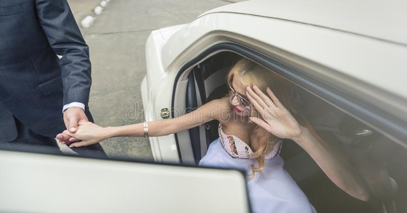 Gentleman helps a beautiful woman stepping out. Young gentleman helps his date stepping out of the limousine, while she hides her face from the camera's stock photography