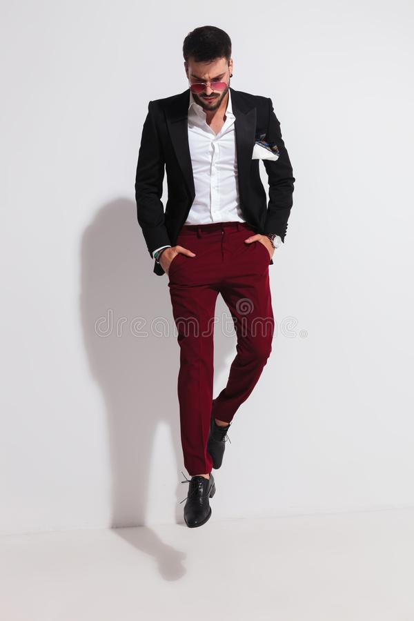 Gentleman jumping with hands in pockets and looking down stock photo