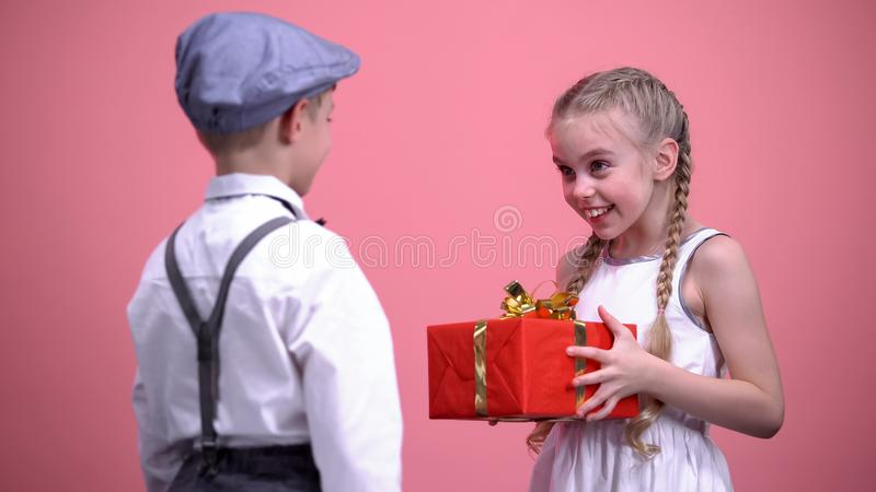 Gentleman kid presenting giftbox to his little girlfriend, birthday celebration stock image