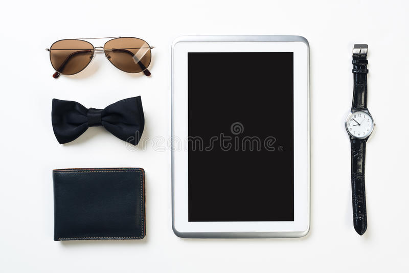 Gentleman kit of tablet watch glasses bow tie and notebook on wooden table. Men`s accessories and tablet on white wooden surface royalty free stock photography