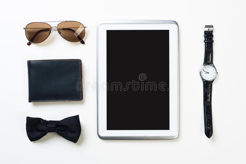 Gentleman kit of tablet watch glasses bow tie and notebook on wooden table. Men`s accessories and tablet on white wooden surface royalty free stock photo
