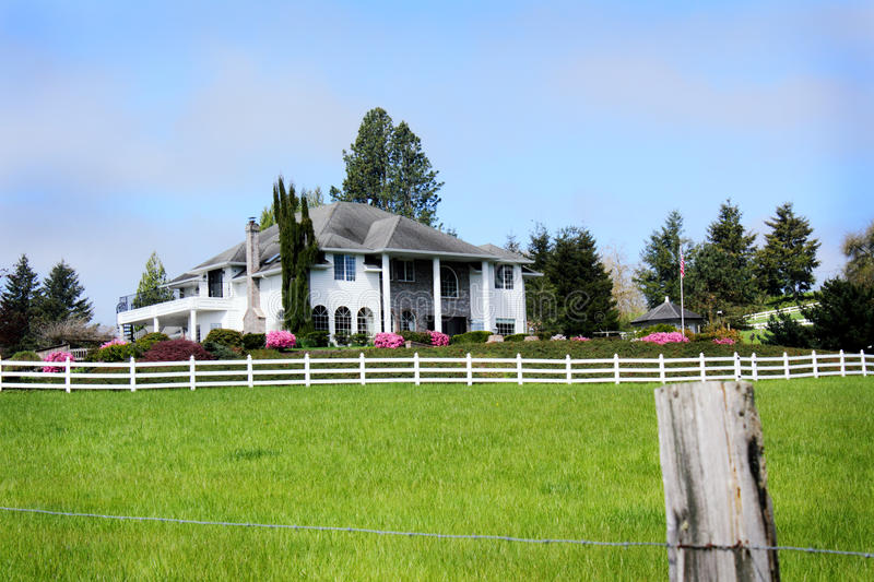 Gentlemans Country Farm Home. Frontal view of an elegant contemporary home in the country with pasture and fences in foreground stock image