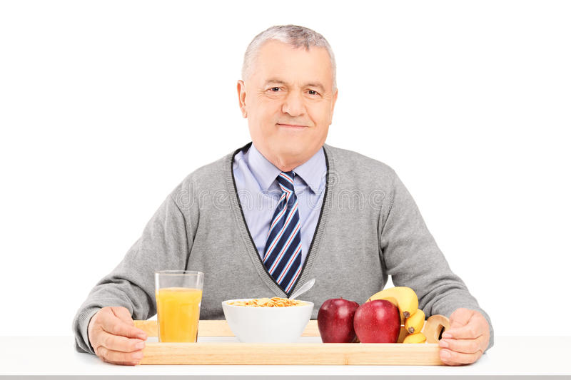 Download A Gentleman Sitting On A Table With A Tray Full Of Drinks And Fo Stock Image - Image: 29888603