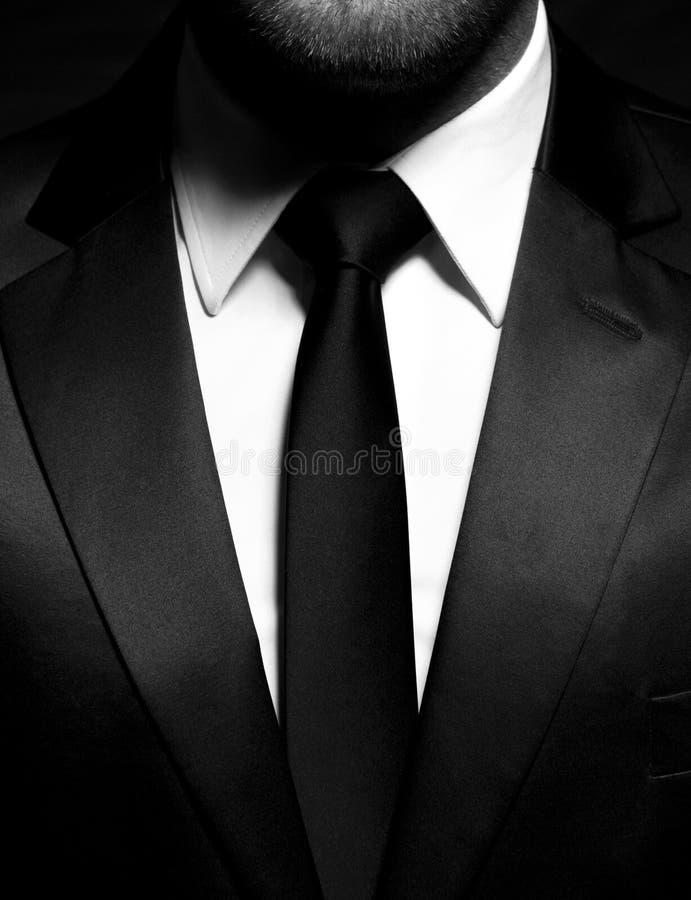 Gentleman som bär en svart dräkt, skjorta och band, smoking royaltyfria bilder
