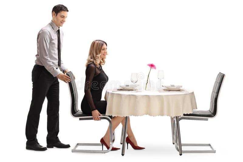 Gentleman som hjälper hans flickvän med stolen royaltyfria bilder