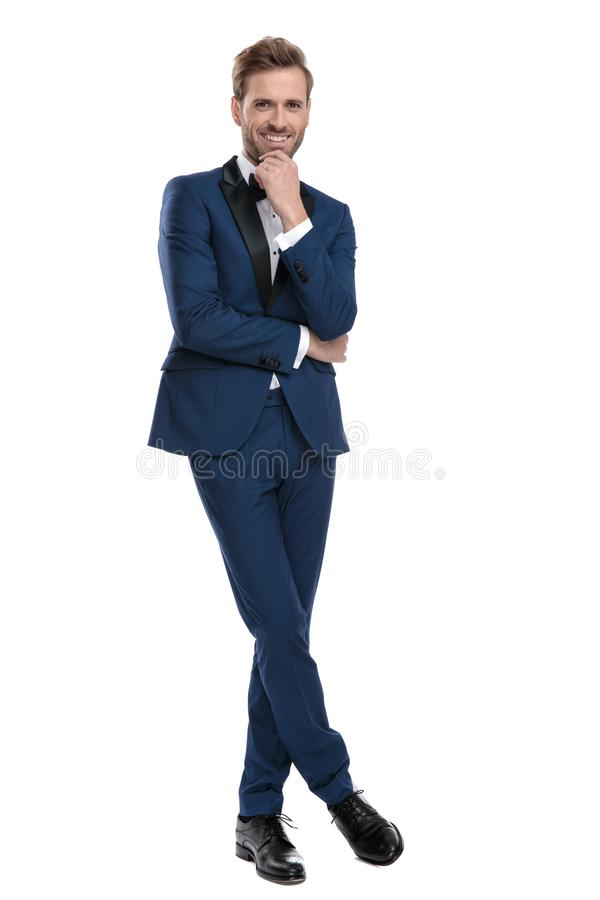 Gentleman is thinking with legs crossed and hands folded. Gentleman in blue tuxedo is thinking with legs crossed and hands folded on white background royalty free stock images