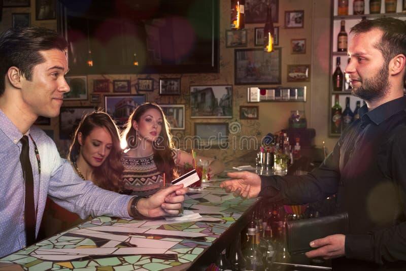 Gentlemannen inviterar hans vänner och lön med kreditkorten på Co arkivbilder