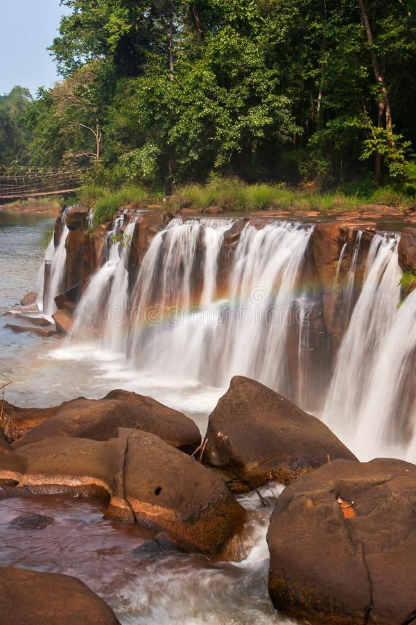 Gently rainbow over tropical waterfall. Tad Pha Suam waterfall in rainy season. Beautiful sandstone and gently waters falling off. The cliff, bamboo bridge royalty free stock photography